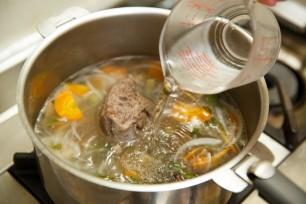 お肉を煮込んでいる途中、水を一定量に保つため水を足す。