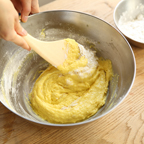 4. ②に振るった強力粉を3回に分けて入れ、木べらで混ぜひとかたまりにする。(③)