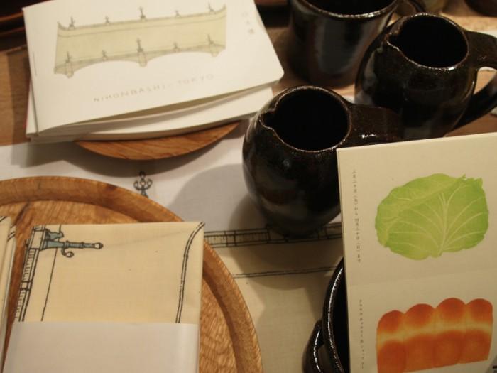 """フィリップ・ワイズペッカーさん描きおろしの日本橋のイラストをあしらった手ぬぐい 1,000円など。『彦坂木版工房「パンとやさい」展』では彦坂有紀さんのパン、野菜の木版画をキッチンリネンやトート、ベビーTシャツ、ノートなどにあしらった""""DO""""とのコラボレーションアイテムも販売。"""