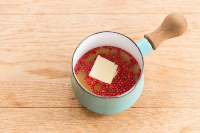【ピンクペッパーのレモンクリームソース】小鍋にピンクペッパー、バター、コンソメを入れ弱火で25分煮る。