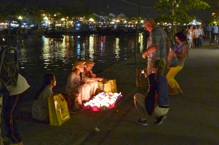 川沿いで灯籠を売る子どものアオザイがあざとい?でも観光地だし。