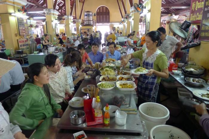 市場の中の屋台に並んで座り、みんないっしょに昼飯だ。