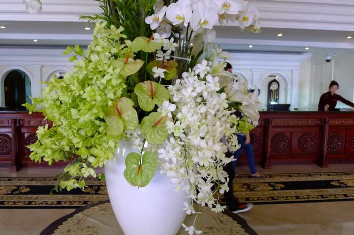 南の国の白い花と、木彫りのカウンターにアオザイの女性
