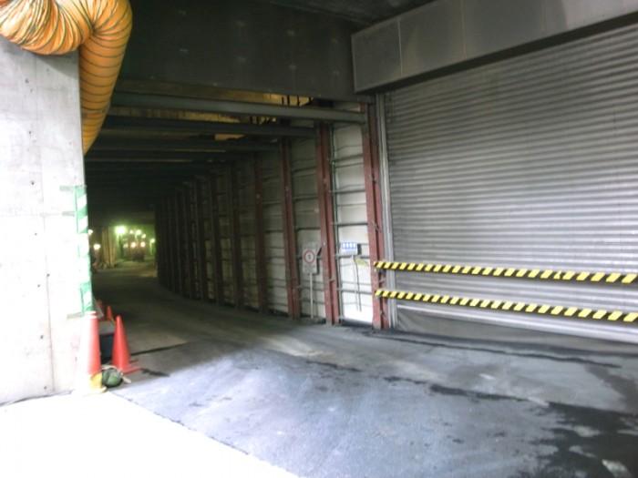 玉川通りに面したところに仮設の入り口が。壁の向こうはすでに供用中の連絡路で、その切れ間から除くとクルマがワルツを踊っているのが見える。左に折れれば品川線に続く工事中の連絡路が。
