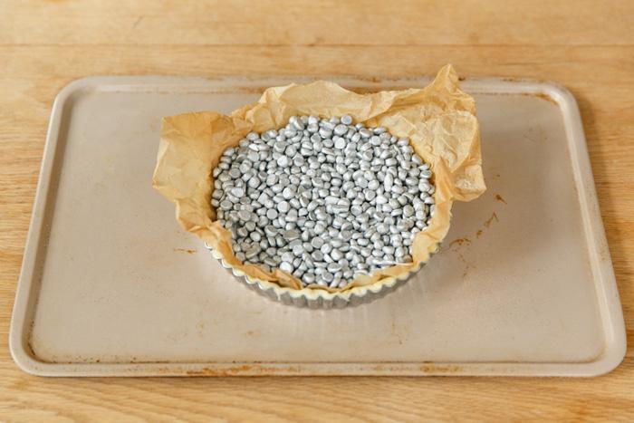 2.クッキングシートやアルミホイルを敷き重しをのせ200℃のオーブンで20分ほど焼き、重しをとって10分焼く。(パイが膨れてしまったらスプーン等で押さえておく。)