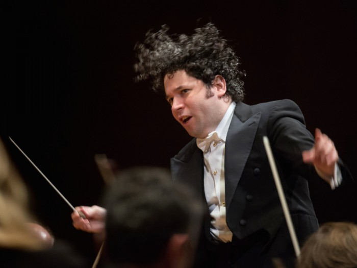 髪を振り乱すドゥダメル。メインの奏者に目線をあわせるように腰を落としまなざしを送る。この上下左右の激しいアクションは、見ているとまるで華麗なるボクサーのしなやかな動きを思い起こさせる。ウィーン・フィルハーモニー管弦楽団 グスターボ・ドゥダメル指揮『ウィーン・フィルハーモニー ウィーク イン ジャパン』  東京・サントリーホールより。photos / Suntory Hall