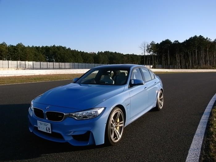 """都心からほんの1時間ちょっとで行くことのできるサーキット、フォレストレースウェイ。M3の試乗車は""""ヤス・マリナ・ブルー""""が鮮やかだった。フロント255/35R19+9J/リア275/35R19+10Jの""""Mライト・アロイ・ホイール ダブルスポーク・スタイリング437M""""は27万8000円高。"""