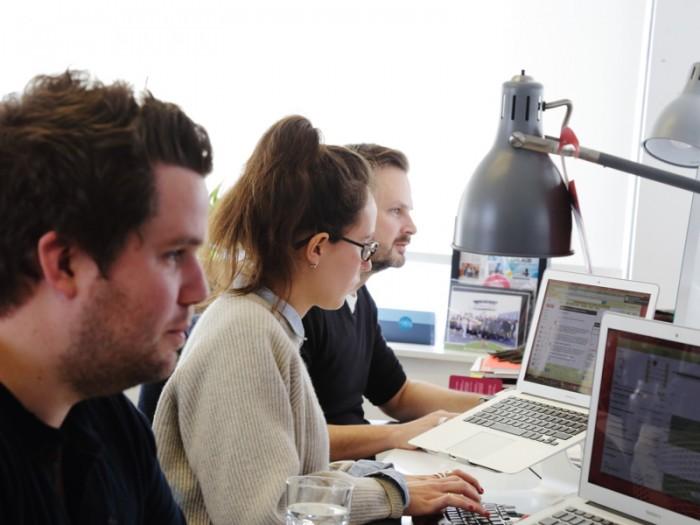 窓から光がいっぱい注ぐオフィスで約20名のスタッフが働く。