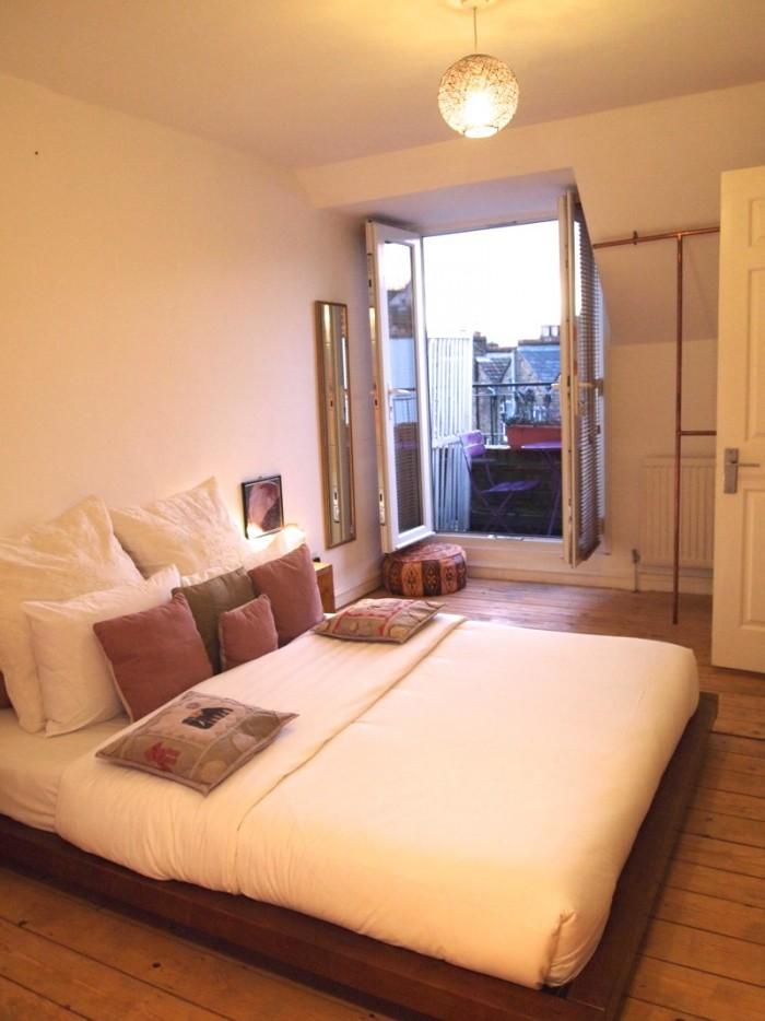 4Fのロフトルーム。木製のフロア、棚、大きめのベッド、アロマ香るソープ類などでリラックス・ムード。