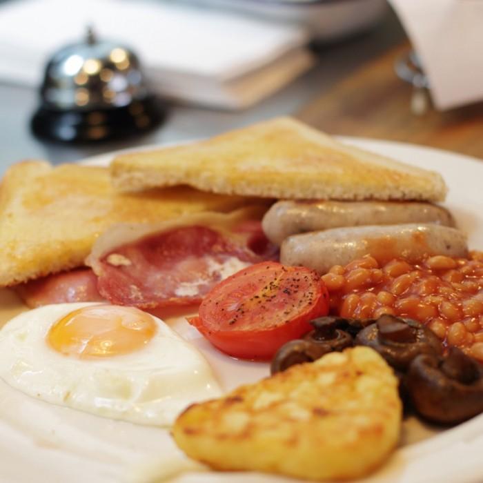 フル・イングリッシュの朝食。ソーセージ、ベーコン、目玉焼き、ローストトマト、ビーンズ、マッシュルーム、ハッシュドポテト、トーストで8.5ポンド。朝は8:00から。