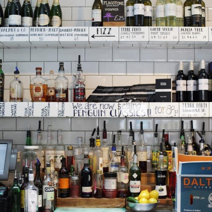 お店を入って正面がオープンキッチン。その奥には白いタイル張りを上手に活用、アルコール類が並んでいます。