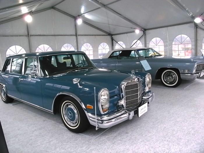 """JAIA(日本自動車輸入組合)設立50周年を記念した特別展示。良くも悪くも""""ガイシャ""""がガイシャであった頃の文字どおり千両役者。1967年キャデラック・ドヴィル(右)と1972年メルセデス・ベンツ600。いずれも全長5.5~5.6m+に及ぶ超大型・超高級車で、中でも後者は世界の王侯貴族やローマ法王に愛用された。かつて取材でオーナーから""""600""""を借り受けて我が家に持ち帰ったら平場のマンション駐車場で鼻先1/3がはみ出してしまい、身の程を思い知らされた。"""