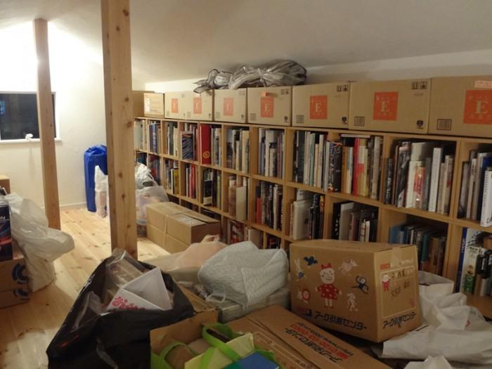 引越で書物搬入中の3階ロフト。反対側の壁も全面が同じような書棚。