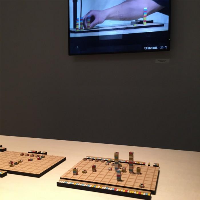 アート部門新人賞、山本 一彰(日本)の『算道』。©2015 Takaaki Yamamoto 縦横に線が引かれた版の上に、特定の性格を持つ駒を並べ将棋を指すように位置を変えて答えを導き出す新しい計算方法。