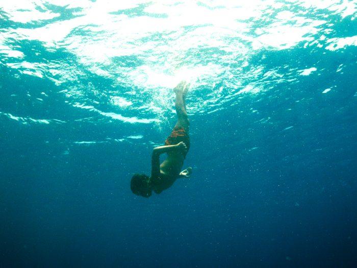 美しい海の中を泳ぎ回っている少年ニコラ。
